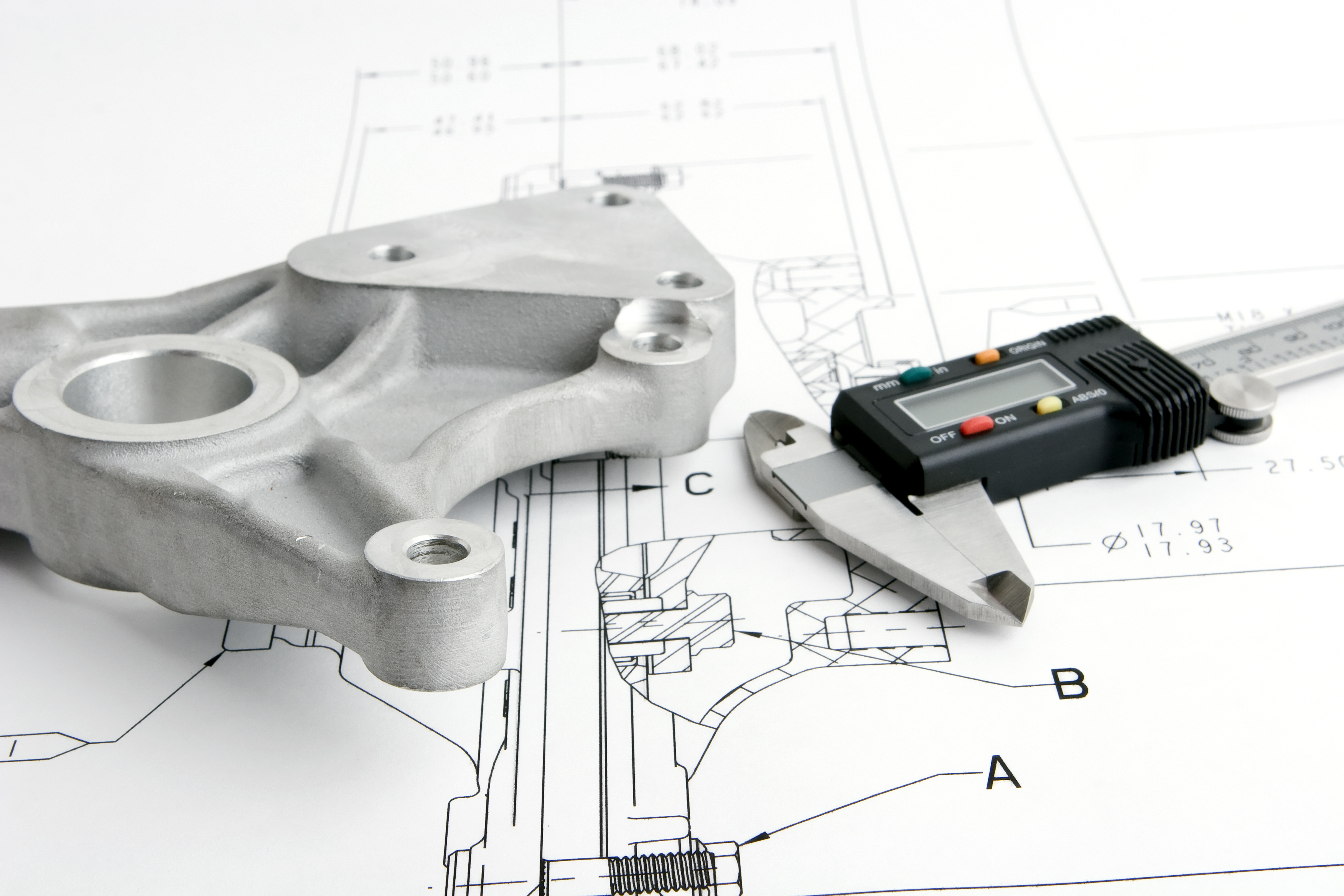 Close up of engineering drawing with callipers focus on metal part